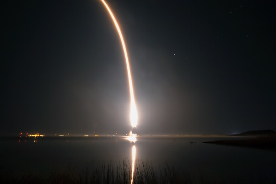 fire trail of a rocket taking off in a night sky