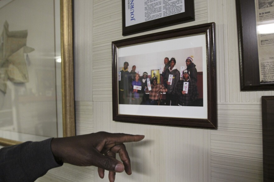 Wendell Harris points to photos and plaques on the wall in his home in Milwaukee.