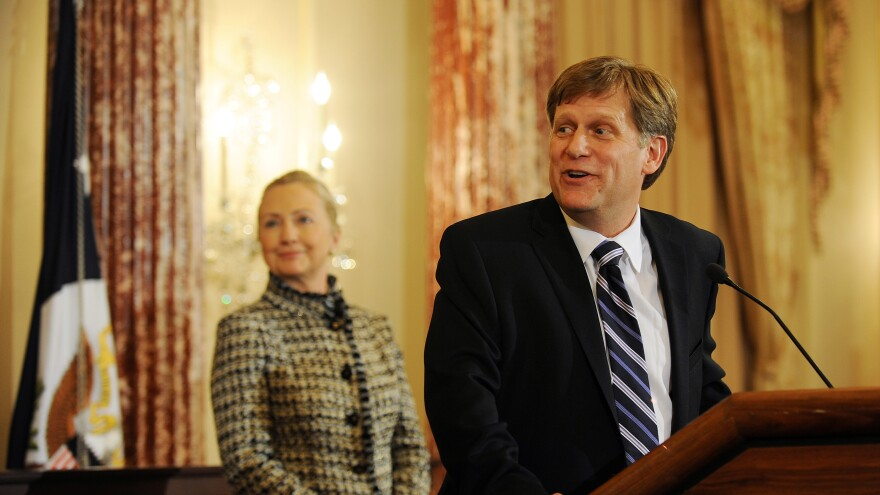 U.S. Secretary of State Hillary Clinton smiles at a remark made by Ambassador-Designate to Russia Michael McFaul during his swearing-in ceremony at the State Department in 2011.