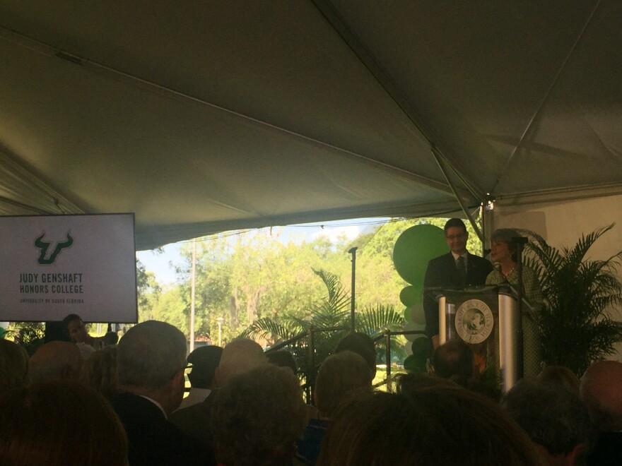 USF System President Judy Genshaft and her husband, Steven Greenbaum, at a podium.