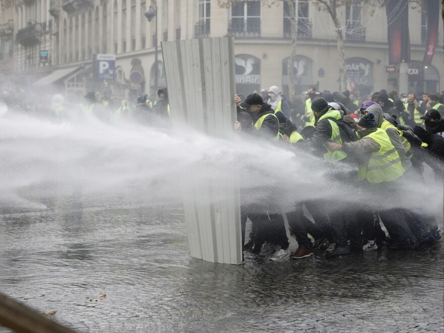 Protesters in Paris form a barrier against police water cannons.