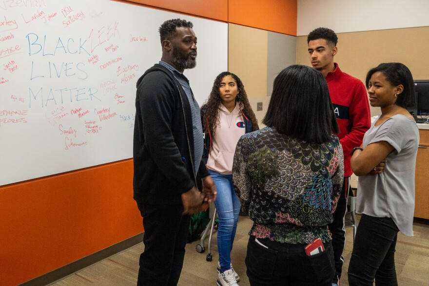 "Picture of an African-American man speaking to a circle of four Black Student Union members. A whiteboard with the words, ""Black Lives Matter,"" is in the background."