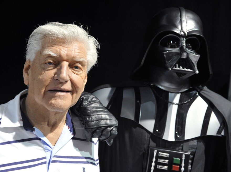 English actor David Prowse, who played Darth Vader in the first <em>Star Wars</em> trilogy poses with a fan dressed up in a Darth Vader costume during a Star Wars convention on April 27, 2013. Prowse died in 2020, at the age of 85.