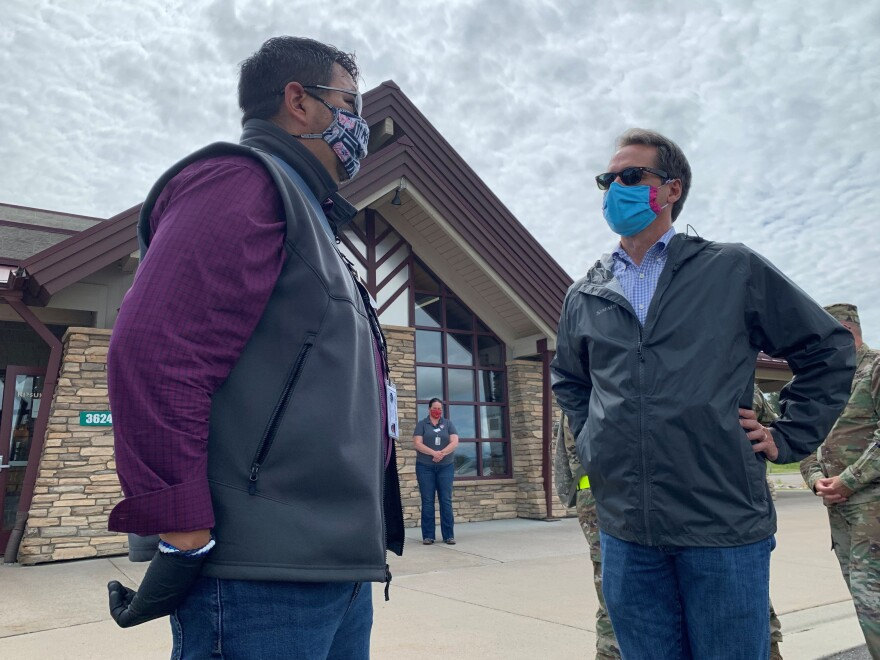 Montana Gov. Steve Bullock, right, gets an update on coronavirus testing from councilman Martin Charlo of Confederated Salish and Kootenai tribes. Montana now has the lowest coronavirus infection rate in the U.S.