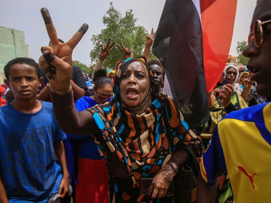 Sudanese protesters flash the V-sign during a mass demonstration in Khartoum on Sunday against Sudan's ruling generals.