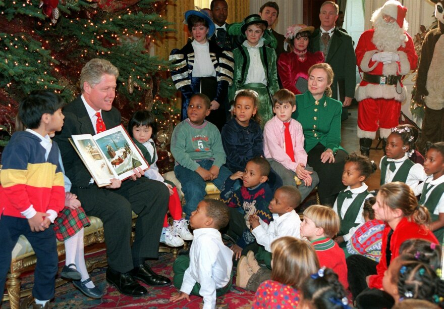 """President Clinton reads <em>""""Twas the Night Before Christmas</em> to children at the White House in 1995, as Santa looks on."""