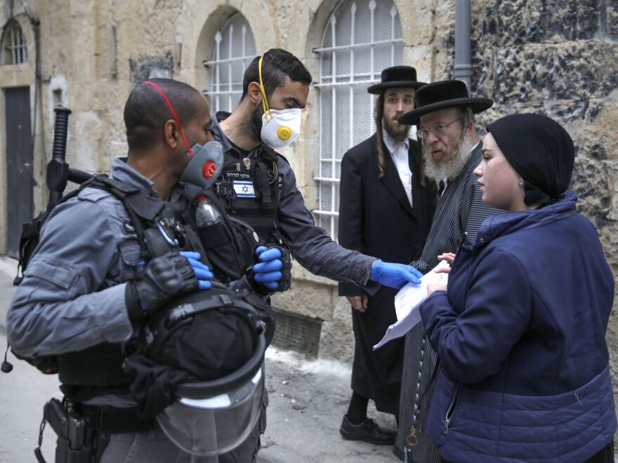 Israeli police officers wearing protective gloves and masks check papers as they enforce restrictions in an ultra-Orthodox Jewish neighborhood in Jerusalem on Tuesday, during a partial lockdown to curb the spread of coronavirus infection.