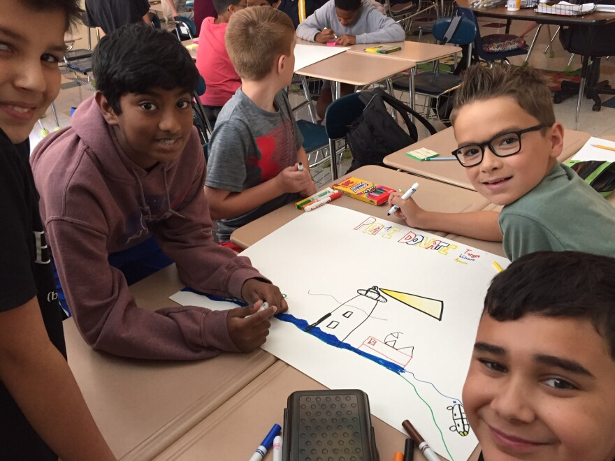 Students in Leslie Nielsen's class at Community House Middle School in Charlotte work on posters seeking gift cards for Ocracoke School, which was damaged during Hurricane Dorian.