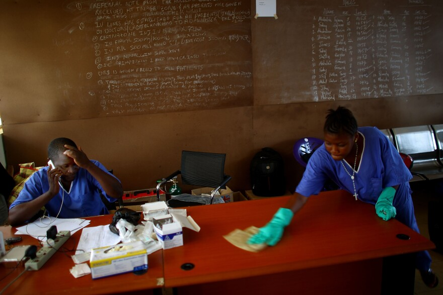 This photo was taken in November, a tough month for Sierra Leone, with Ebola cases reportedly on the rise. A staff member is disinfecting an office where Dr. Komba Songu M'Briwah talks on the phone.