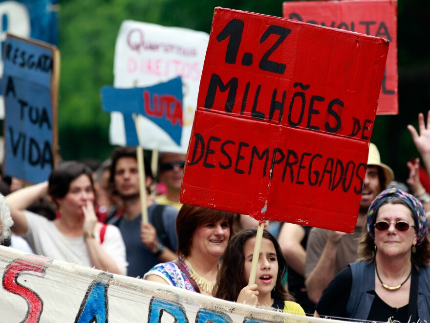 """A young girl holds a sign with the words """"1.2 Million Unemployed"""" during an anti-austerity protest in Lisbon on May 12, 2012."""