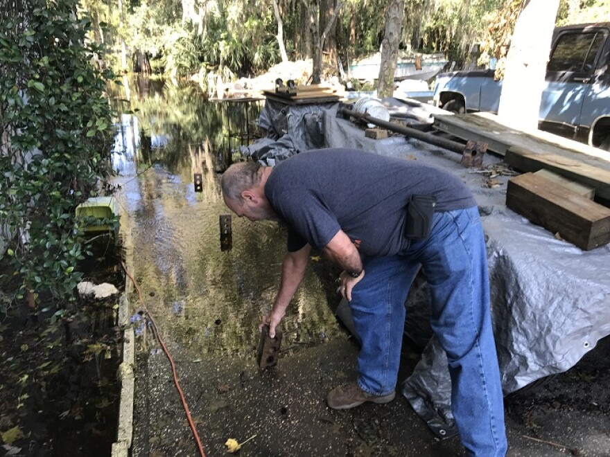 A man uses bricks to measure the Irma-related flooding in his Pasco County yard Friday.