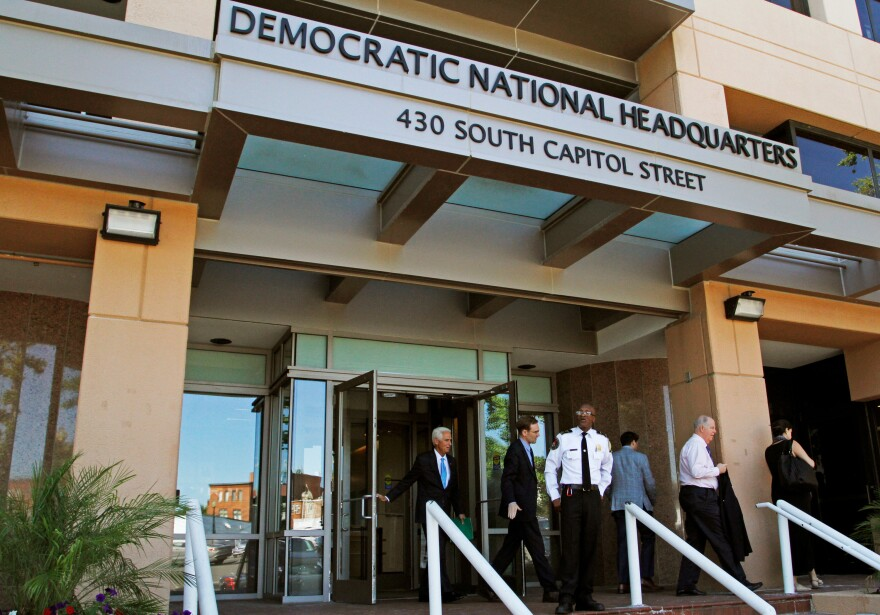 "People stand outside the Democratic National Committee headquarters in Washington, D.C., in June. DNC staffers said publication of leaked emails in July was a Russian ploy to support the candidacy of Donald Trump. But, says a Russian investigative journalist, ""I think it's not about Trump. It's all about Hillary Clinton."""