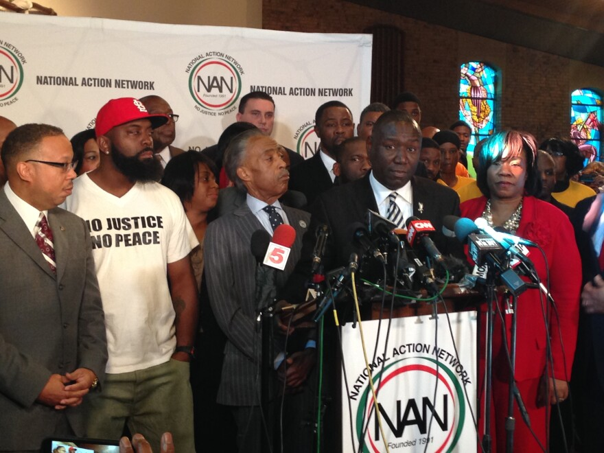 At a press conference in 2014, Benjamin Crump (at podium) stated Michael Brown Jr's family will move forward after learning former Ferguson police officer Darren Wilson was not indicted for the killing of Brown.