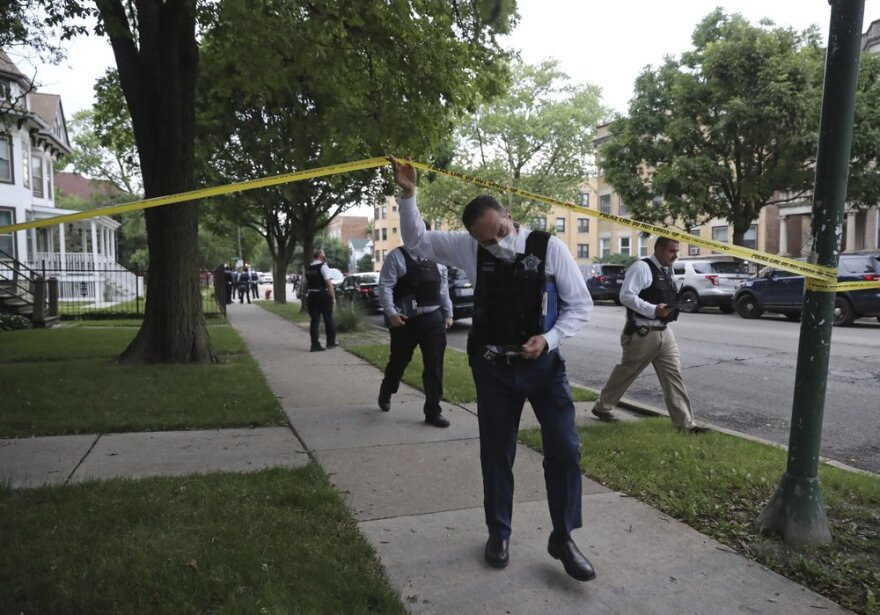 Police detectives canvas the area where a 3-year-old boy was fatally shot while riding in an SUV with his father, near the intersection of North Central Avenue and West Huron Street in Chicago's Austin neighborhood June 20.