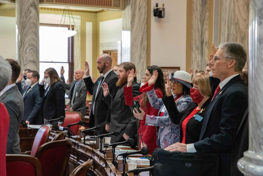 Legislators raise their hands to be sworn in to the Montana House of Representatives January 4, 2021.