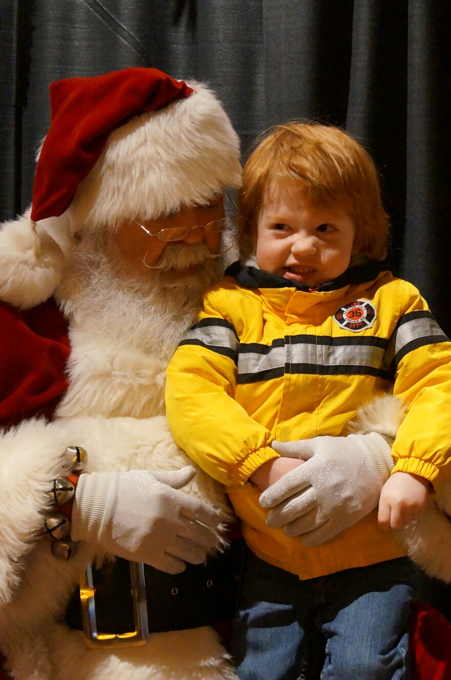 Steve Haws, aka Santa Claus, has been taking toy orders from kids for decades. Here he is with Finn Reynolds.