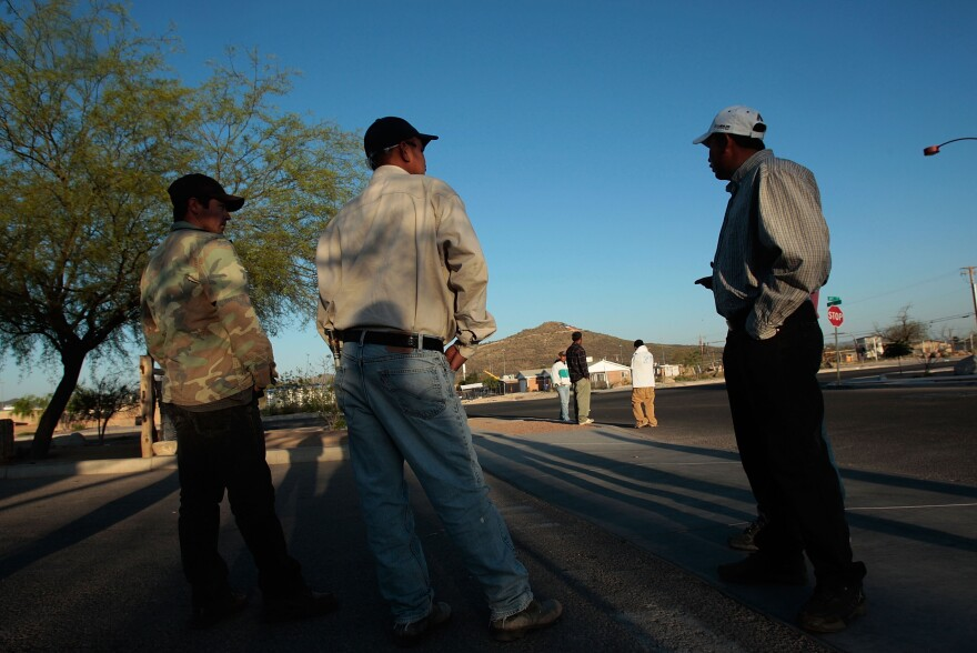Day laborers wait on at a street corner in Tucson, Ariz., hoping for an employer to drive up and put them to work. The photograph was taken in 2008.