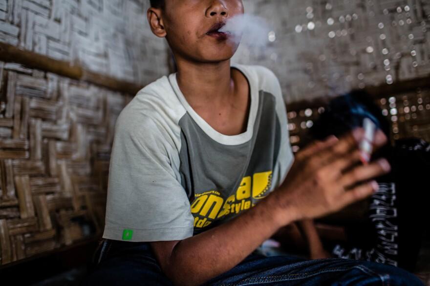 A boy has a smoke in Yogyakarta, Indonesia.