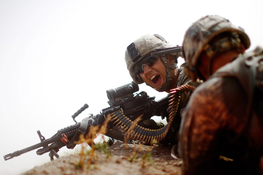 During an all-day gunfight, Spc. Jotiyar Saaty, with Bravo Company, 101st Airborne Division yells for more ammunition while trying to suppress heavy enemy fire.
