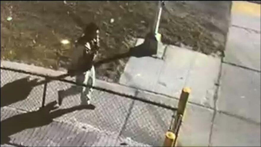 Surveillance video shows overhead view of man walking near fence