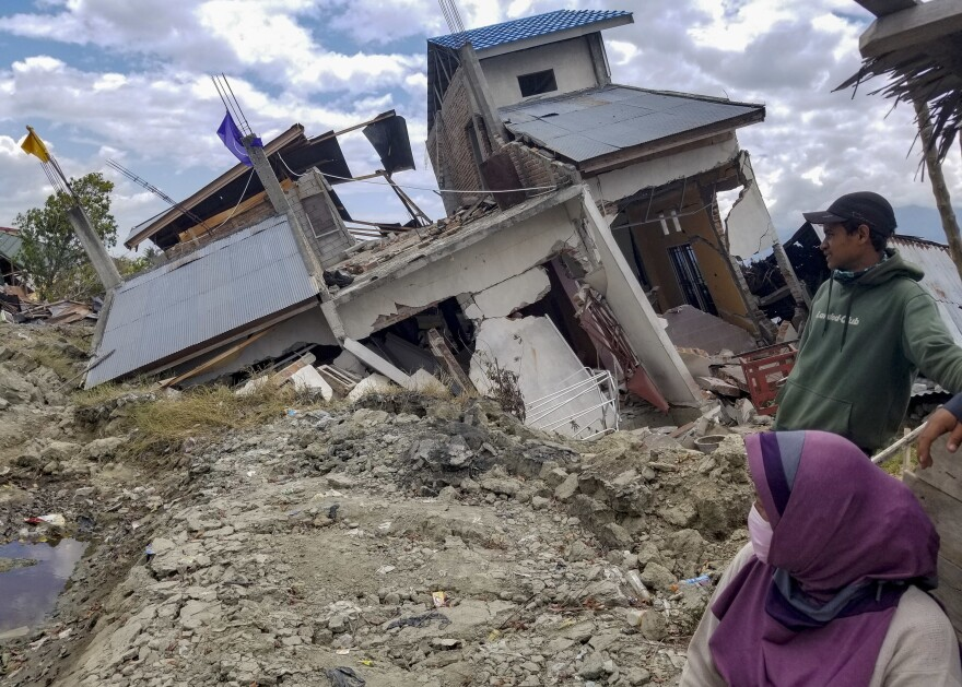 Vera Rahayu Putri and her husband Faizal, who goes by one name, survey earthquake damage in their Palu neighborhood of Petobo, now covered by mudslides. Putri€'s 9-year-old son, Raldi, is among thousands of children who are unaccounted for.