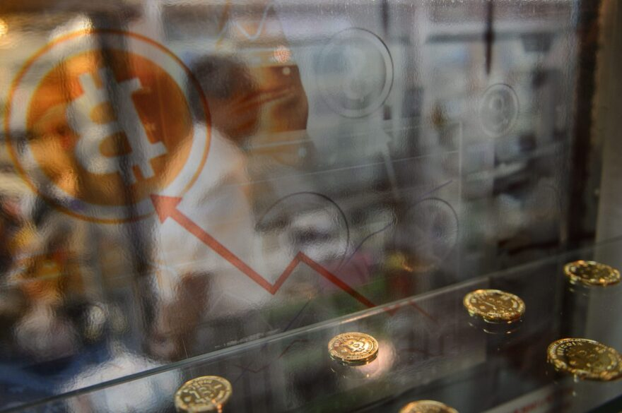 A man walks past a display cabinet containing models of Bitcoins in Hong Kong on Aug. 3, 2016. (Anthony Wallace/AFP/Getty Images)
