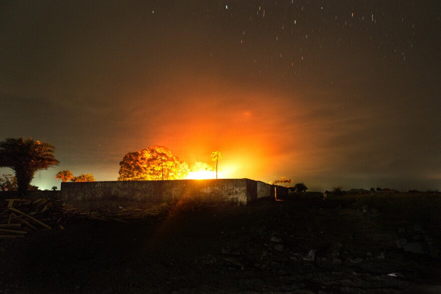 The glow from a crematorium fire lights up the night sky where bodies of people who died from Ebola are cremated in Monrovia, Liberia.