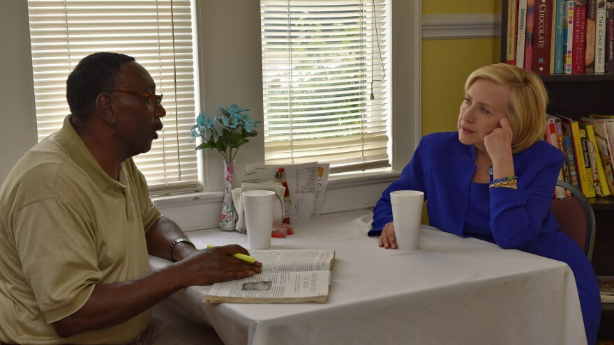 Democratic presidential hopeful Hillary Clinton speaks with Frederic Hunt, a minister at First Calvary Baptist Church, during a campaign stop Wednesday at The Main Street Bakery in Columbia, S.C.