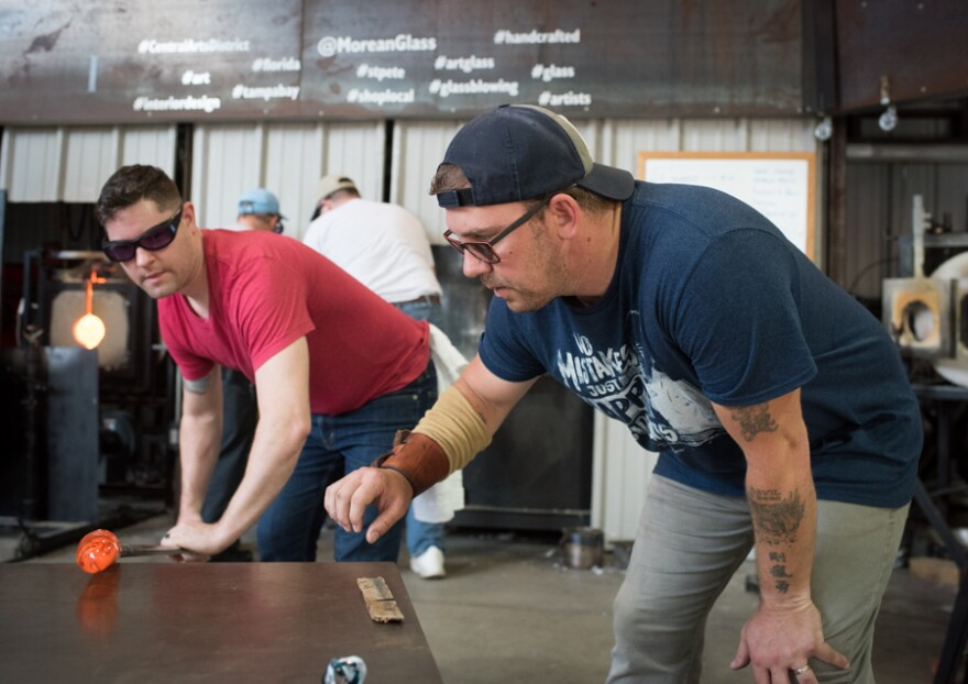 Veteran glassblowers work together to create a piece of art.