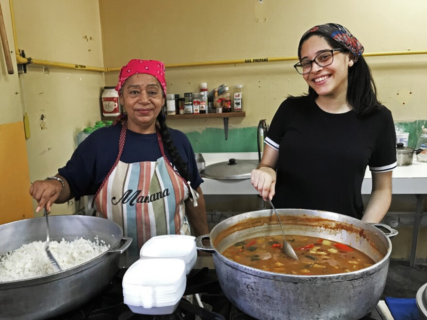 Mariseli O'Neill Fontana (right) and other volunteers serve food three times a week in Las Carolinas, a neighborhood in Caguas.