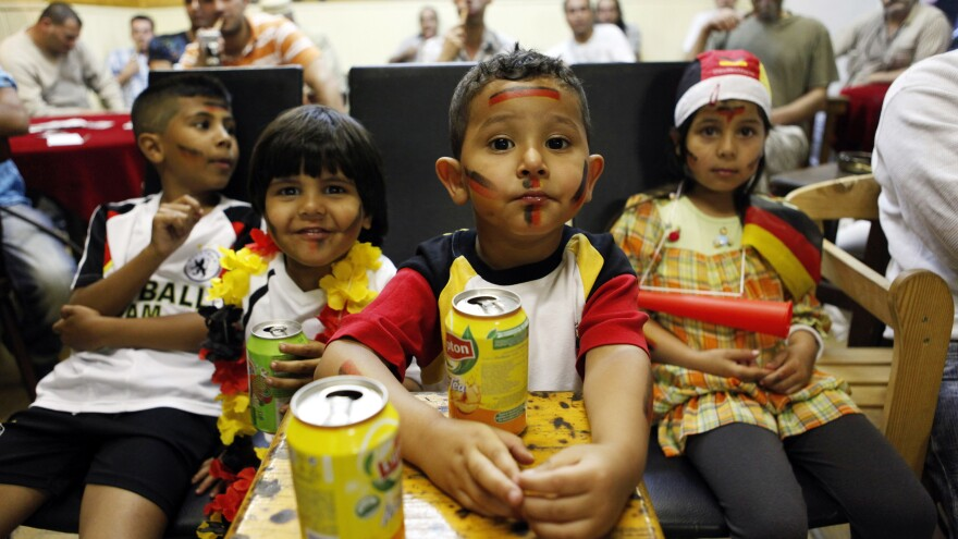Young fans of the German national soccer team drink iced tea in July 2010 as they watch the FIFA World Cup semi-final match Germany vs. Spain in an Arabic cafe in Berlin's Neukölln district. The neighborhood has gentrified rapidly in recent years, but many of the white families moving in leave once their children reach school age. Local groups are trying to change that.