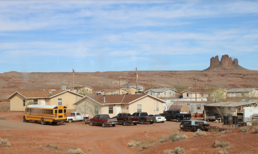 houses with homes in red dirt landscape with craggy rock formation in background