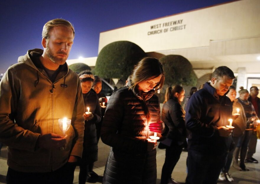 Church and community members, including Matt Pacholczyk and his wife Faith Pacholczyk, stand outside West Freeway Church of Christ for a candlelight vigil Monday night.