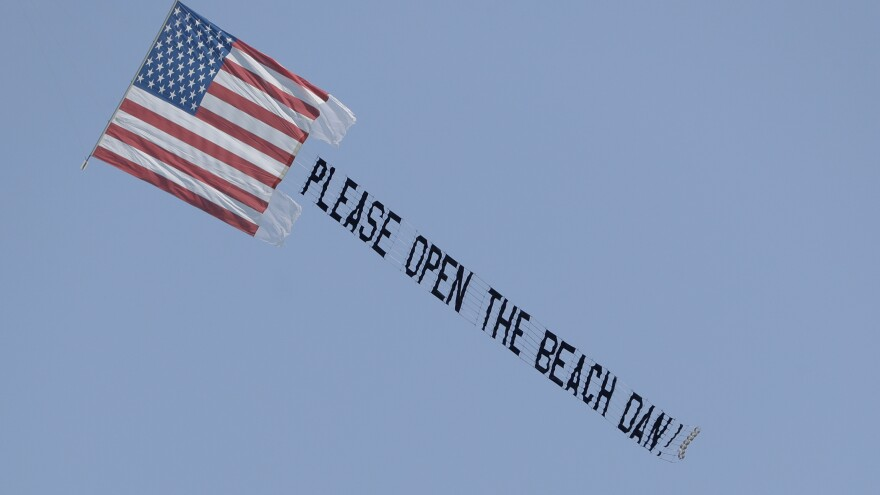 Florida Gov. Ron DeSantis Santis allowed beaches to reopen on April 17, but some officials around the state aren't following his lead. A banner plane flies a sign on April 19 urging Miami Beach Mayor Dan Gelber to open the beaches. Gelber has said the beaches there are unlikely to reopen before June.
