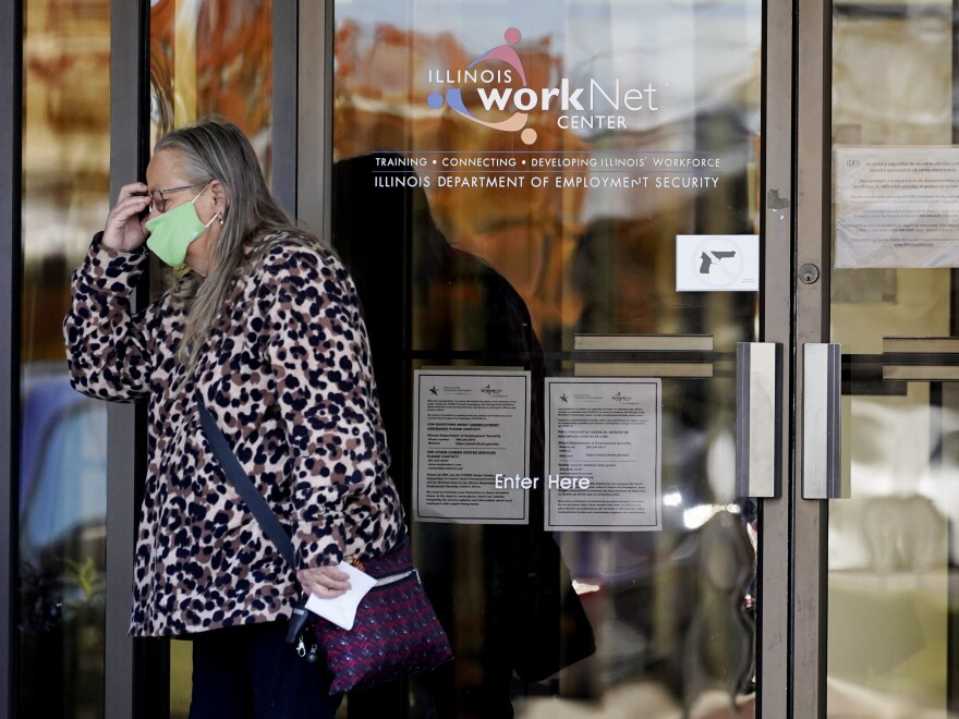 A woman reacts as she leaves the Illinois Department of Employment Security WorkNet center in Arlington Heights, Ill., on Thursday. The state has reported a spike of nearly 10,000 new coronavirus cases. It also reports biggest spike in unemployment claims of all states due to the pandemic.