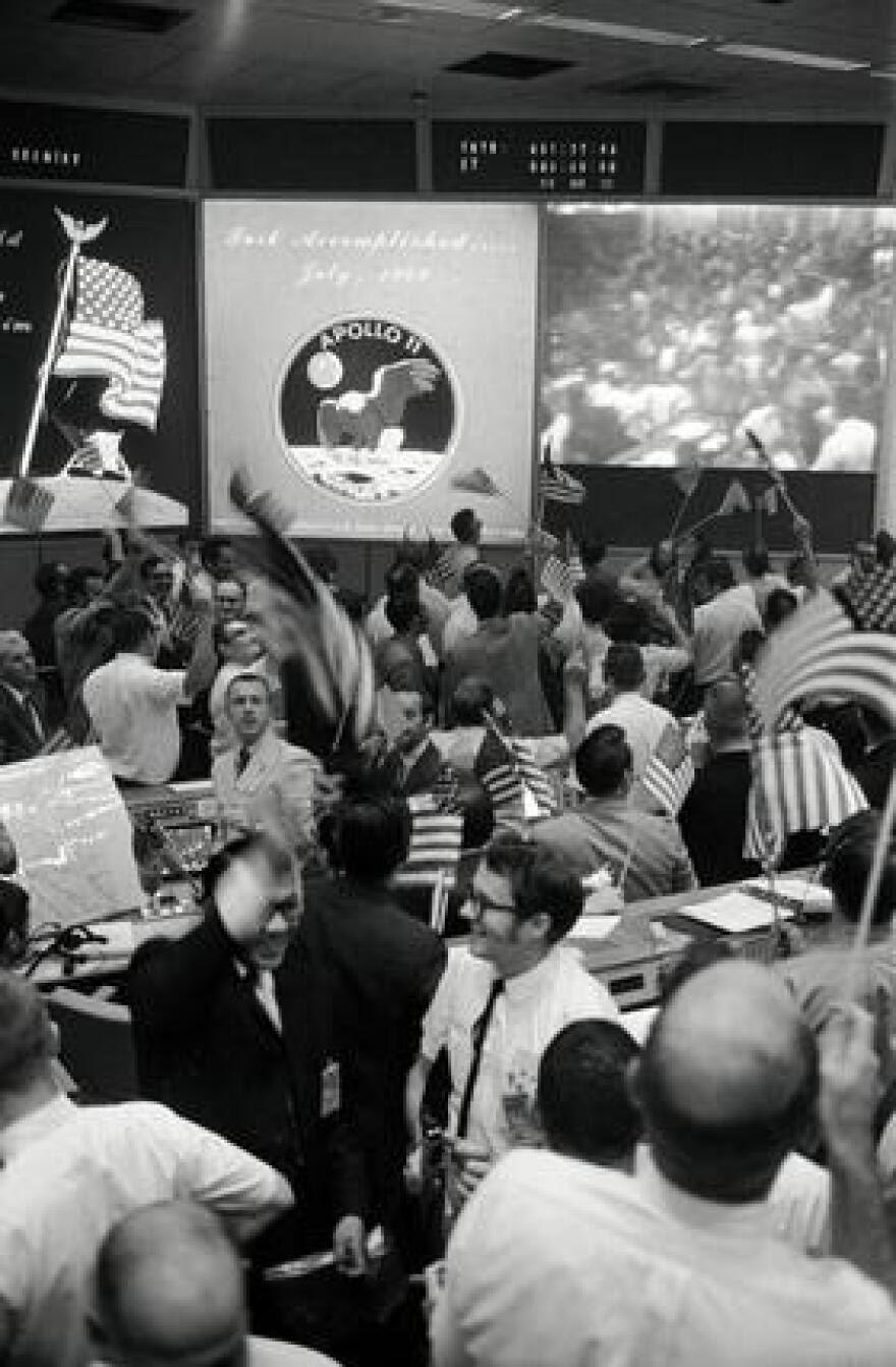 Flight controllers celebrate the successful conclusion of the Apollo 11 lunar landing mission on July 24, 1969, at NASA's Mission Control Center in Houston.