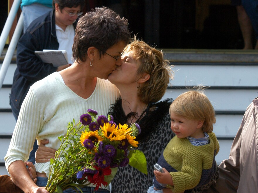 Suzanne Rotondo of New York holds daughter Phoebe while kissing Kristi Habedanck after they receive a marriage license in Provincetown, Mass., on May 17, 2004.