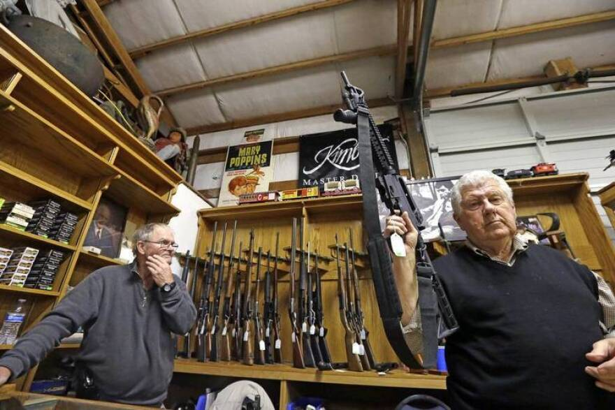Sales clerk Tom Wallitner holds up a Mossberg 715T .22-caliber semiautomatic rifle during an auction at Johnny's Auction House in Rochester, Wash. Most Florida voters favor stricter gun laws and a ban on assault weapons, a new poll says.