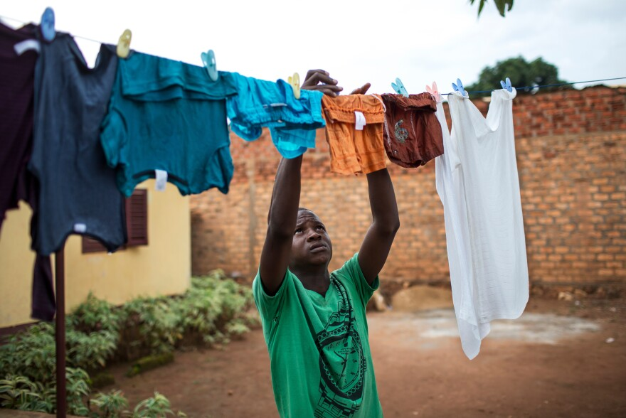 Ghislain-Oxwold Ngoaporo, a 17-year-old member of the Flambeaux scouts, hangs up laundry at his home in Bangui. Members of the scouts learn to be responsible for household tasks like laundry, cooking and cleaning — roles typically delegated to women in the Central African Republic.