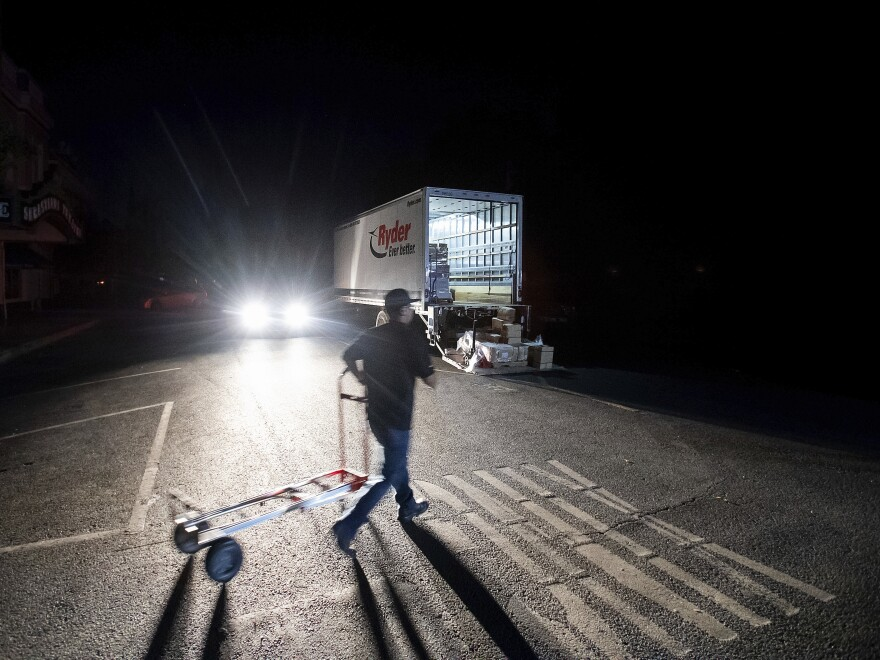 Armando Espinoza delivers paper products to a cafe in downtown Sonoma, Calif., where power is turned off, on Wednesday. Pacific Gas & Electric has cut power to more than half a million customers in Northern California hoping to prevent wildfires during dry, windy weather throughout the region.
