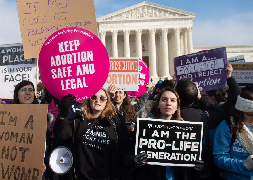 Pro-abortion-rights activists hold signs alongside anti-abortion-rights activists outside the Supreme Court last month.