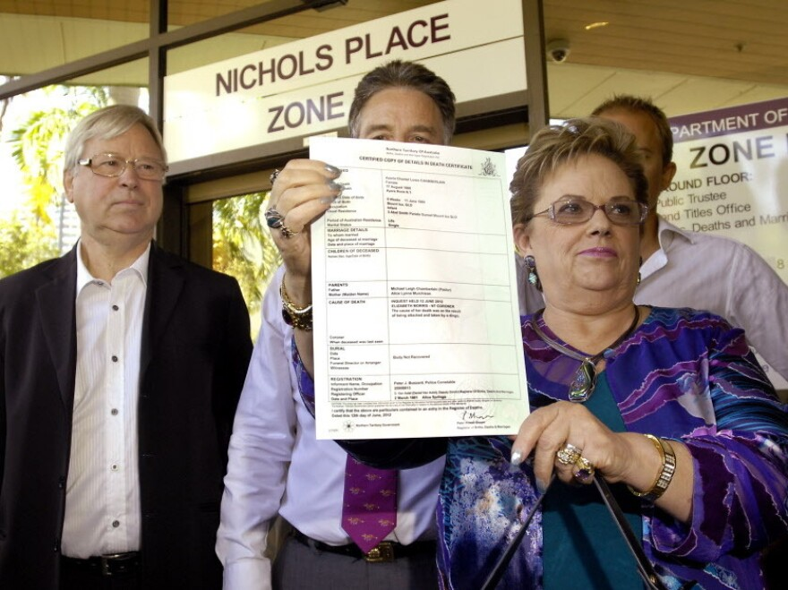 Lindy Chamberlain-Creighton holds her daughter Azaria's death certificate as ex-husband Michael Chamberlain (left) looks on after a coroner ruled today that a dingo snatched the baby from a tent in the Australian desert 32 years ago.