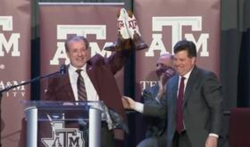 Jimbo Fisher accepts a gift of new boots from Texas A&M University.
