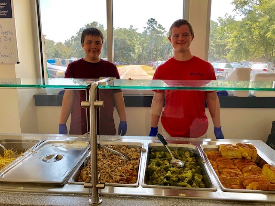 Progressive Pediatric students Roderick Branch and Walker Johnson are standing behind large trays of food during a field trip at the Maclay School dining hall.