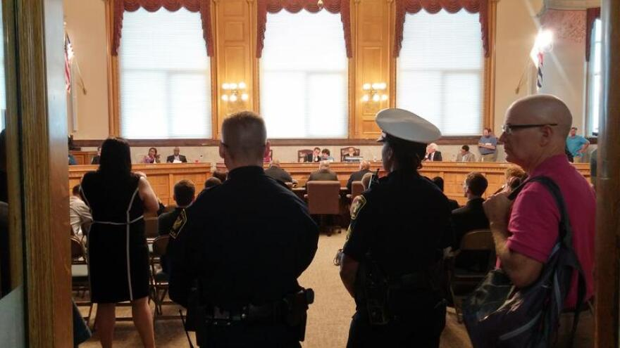 Police officers stand at the back of Cincinnati Council chambers during a meeting discussing the firing of Chief Jeffrey Blackwell.