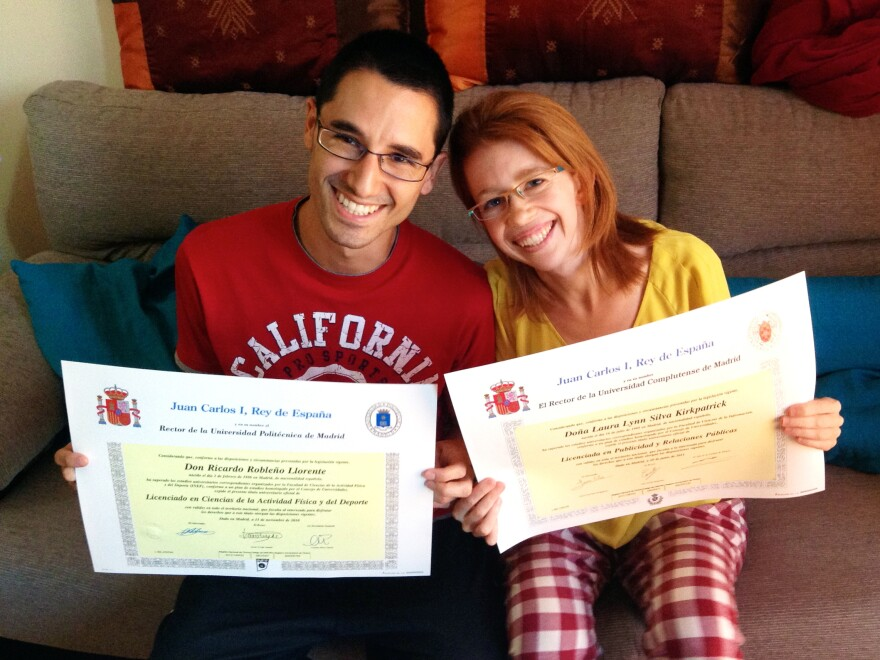 """Ricardo Robleño Llorente and his wife, Laura Silva Kirkpatrick, show their college degrees at home in Madrid. Even though they have two bachelor's degrees and a master's between them, they were unable to find permanent work through most of their 20s, during Spain's economic crisis. """"Why bother going to college at all?"""" Silva Kirkpatrick asks."""