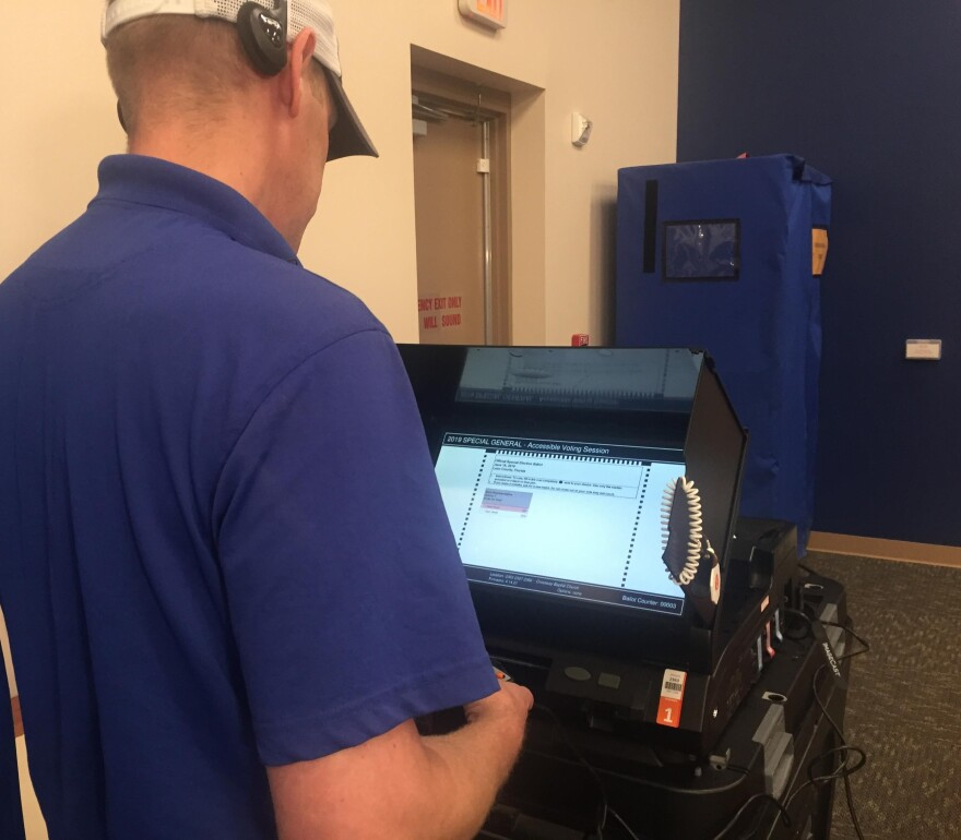 Man stands at voting machine to cast his ballot.