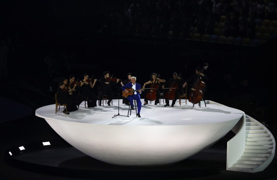 Musician Paulinho da Viola plays (and sings) the national anthem on acoustic guitar, accompanied by the audience and a small string orchestra.