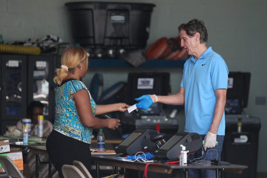 A poll worker in Miami Beach checks in George Hanley, who is wearing protective gloves, as he prepares to cast a ballot during the Florida presidential primary as the coronavirus pandemic continues.
