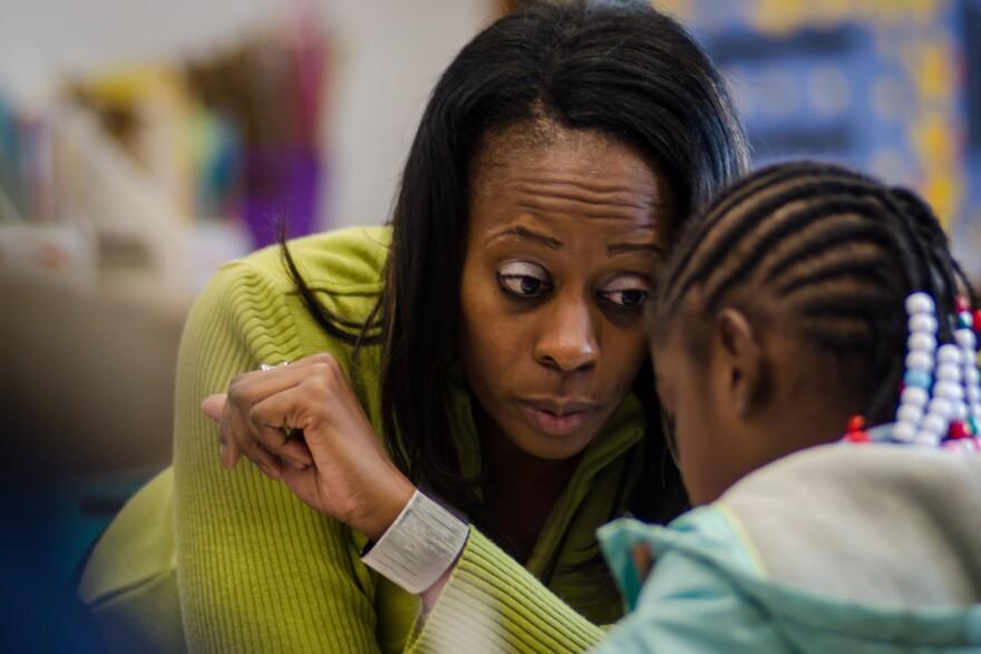 Iris Jackson helps a first-grade student understand an assignment.